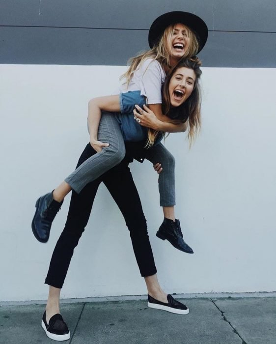 woman carrying her friend smiling