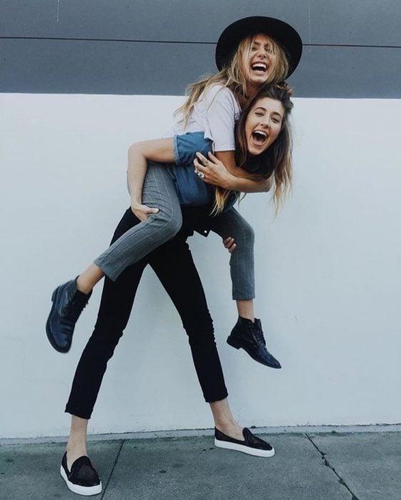 mujer cargando a su amiga sonriendo