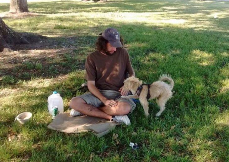 hombre con gorra y perro en el pasto