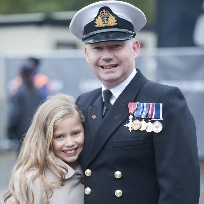 hombre militar abrazando a niña rubia