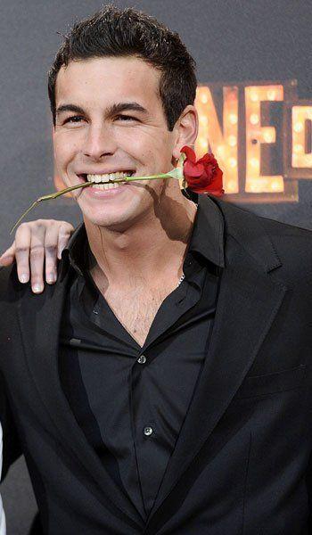 Mario casas con una flor en la boca.