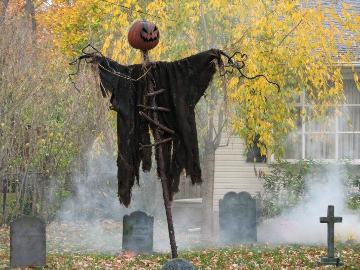 figura de miedo con calabaza y cementerio