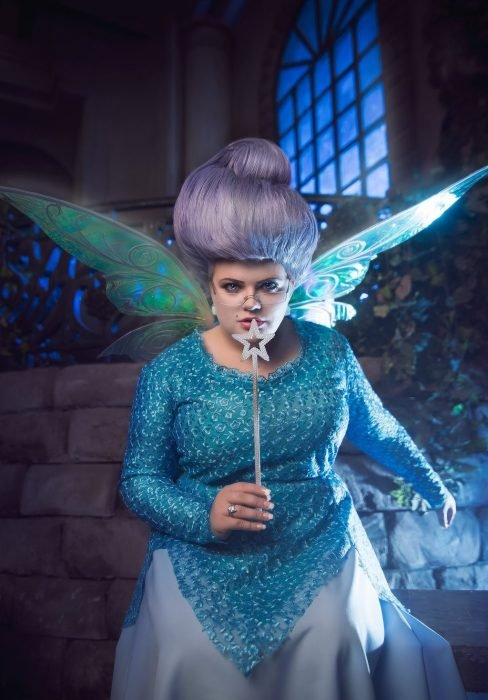 mujer con disfraz de hada madrina, halas y varita magica