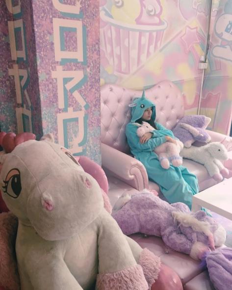 Muchacha recostada en una de las salas de este café de unicornios.