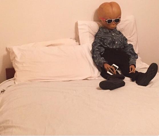 Extraterrestre sentando en una cama con un celular en la mano.