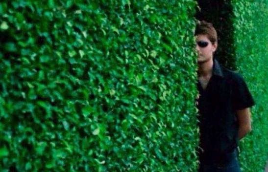 Chico espiando detrás de una pared.
