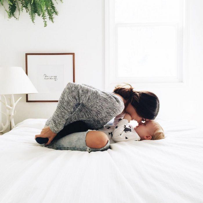 mujer sentada en la cama con bebé
