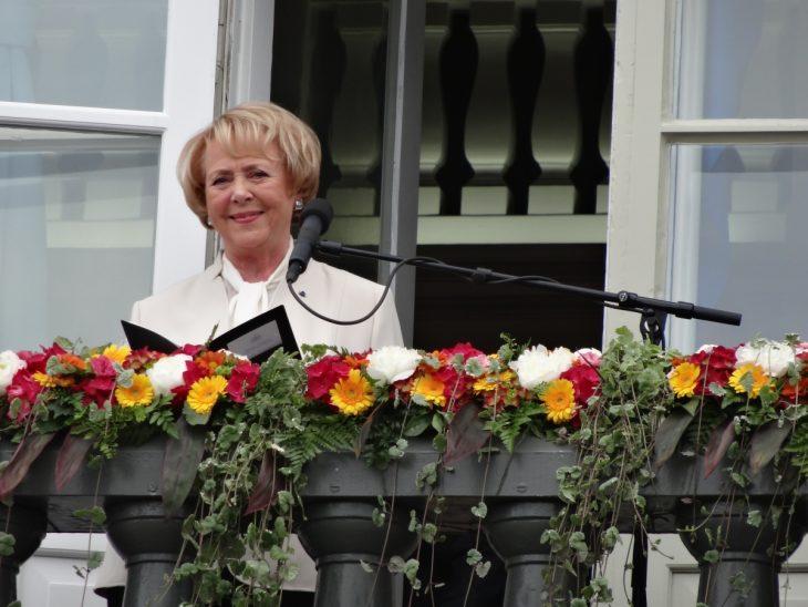 mujer rubia en balcon y con microfono