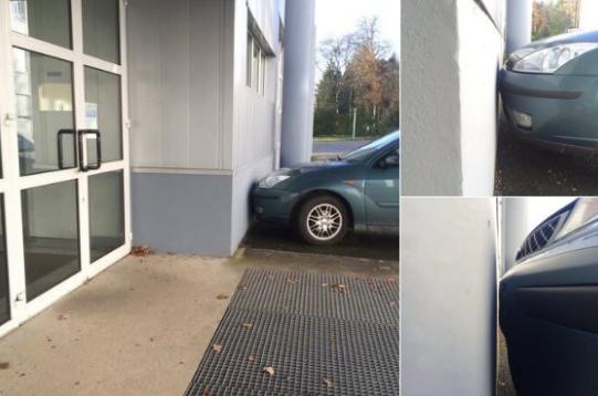 Foto de una carro muy pegado a un pared.