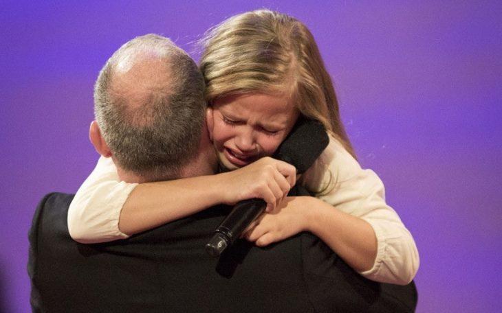 niña rubia abrazando a hombre