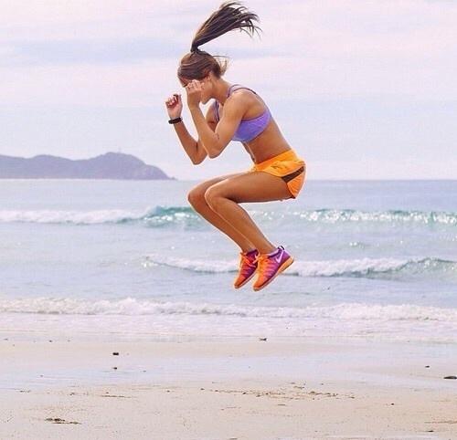 Muchacha saltando en la playa.