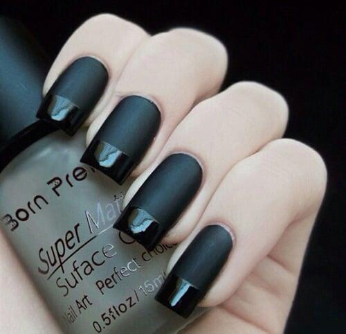 Uñas negras con la punta brillante.