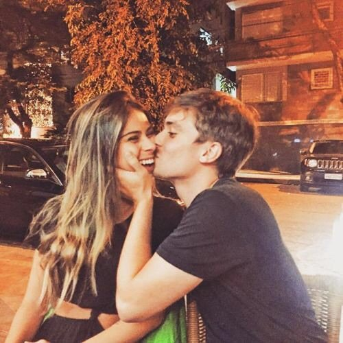 Hombre besando a una mujer en la mejilla.