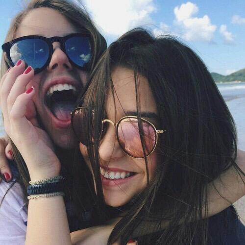 Amigas abrazándose mientras sonríen.