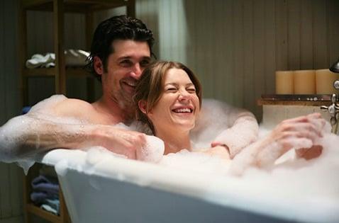 Pareja riendo mientras se baña en una tina.