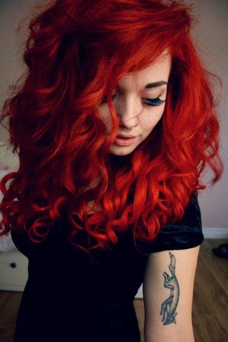 Chica con cabello color rojo ondulado.
