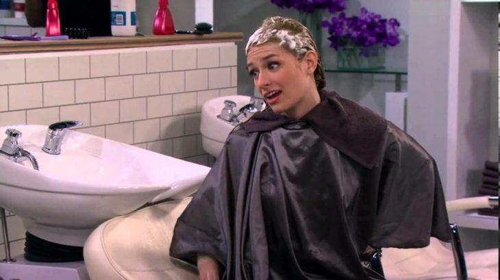 Escena de la serie two broke girls chica con el cabello lleno de espuma en el salón de belleza