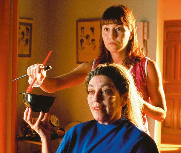 Mujer pintando el cabello de otra