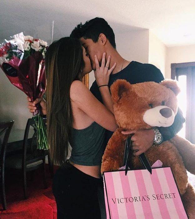 Pareja de novios besándose mientras se dan presentes