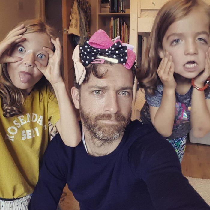 padre al lado de niñas rubias con moños en su cabeza