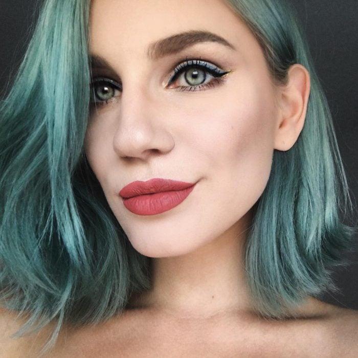 mujer de cabello azul maquillada