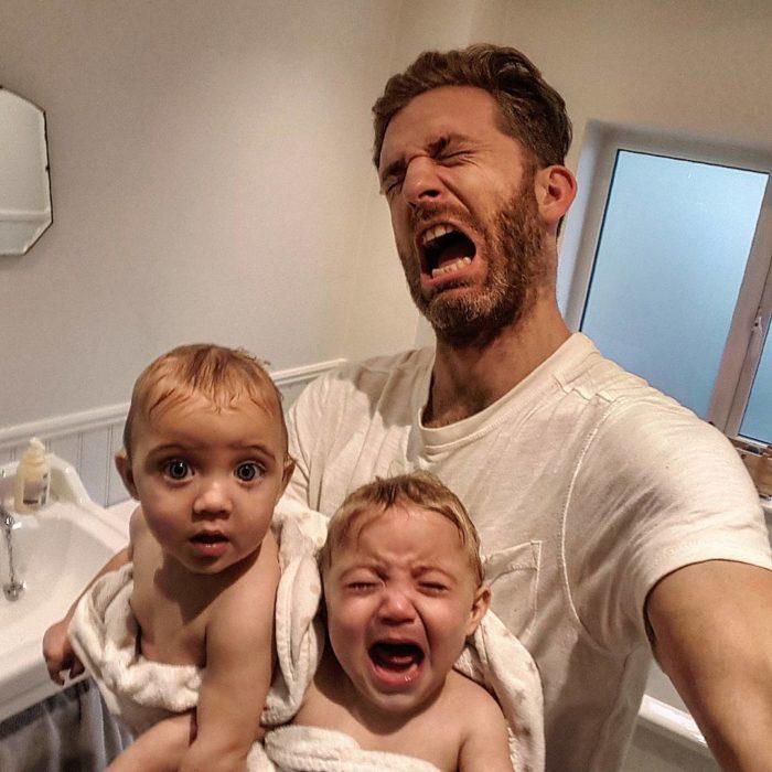 hombre gritando junto a gemelas bebe
