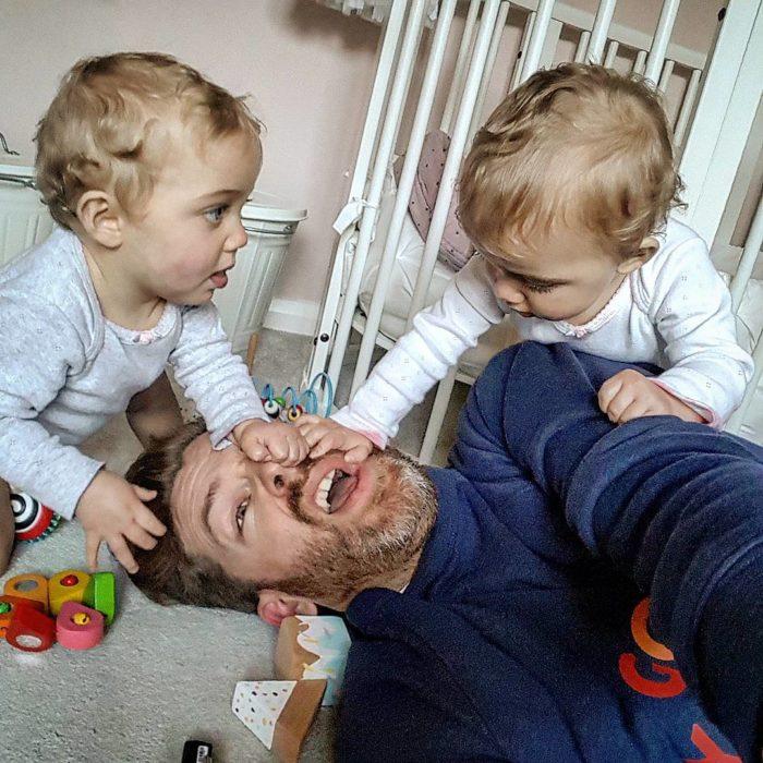 hombre en el suelo y niñas gemelas jugando con el