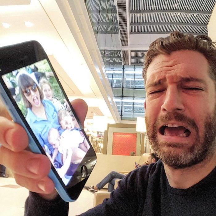 hombre hace cara de tristeza y celular con foto de su familia
