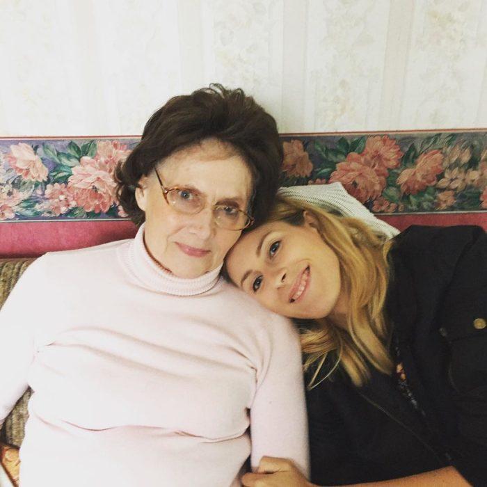 blonde girl hugging grandmother in armchair