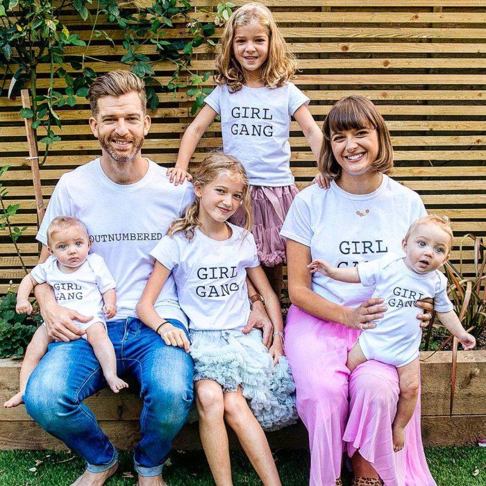 hombre y mujer junto a niñas con playeras blancas