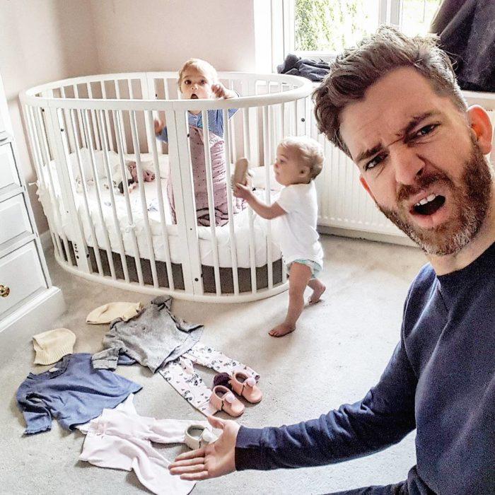 hombre al lado de cuna junto a bebes gemelas