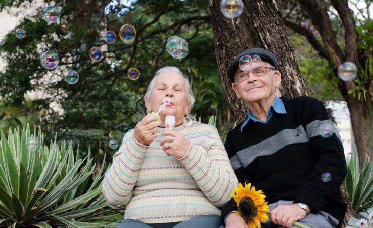 hombre y mujer jugando con burbujas y una flor