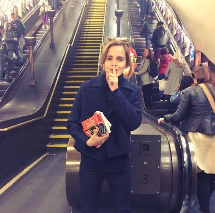 mujer con libros pone su dedo en la boca