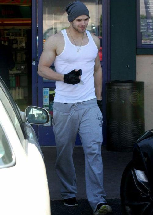 Chico caminando por la calle usando una camisa de tirantes