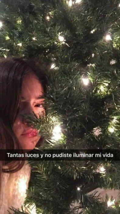 mujer al lado de un árbol de navidad