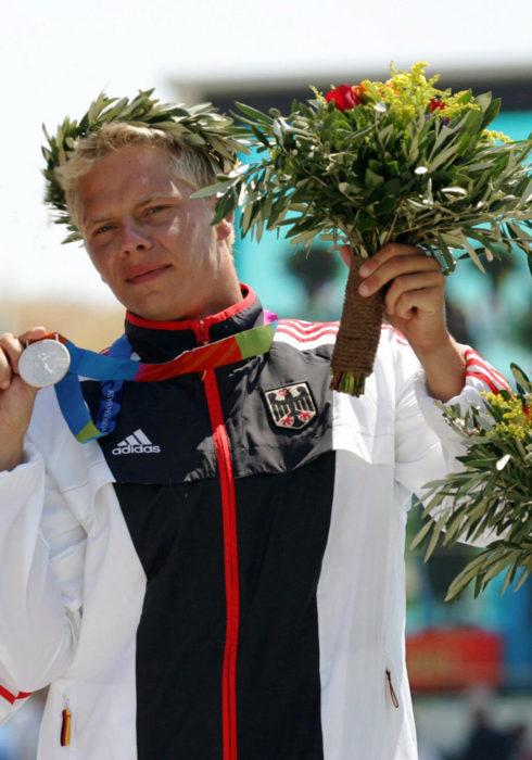 Stefan Henze alzando una medalla de plata en los juegos olímpicos