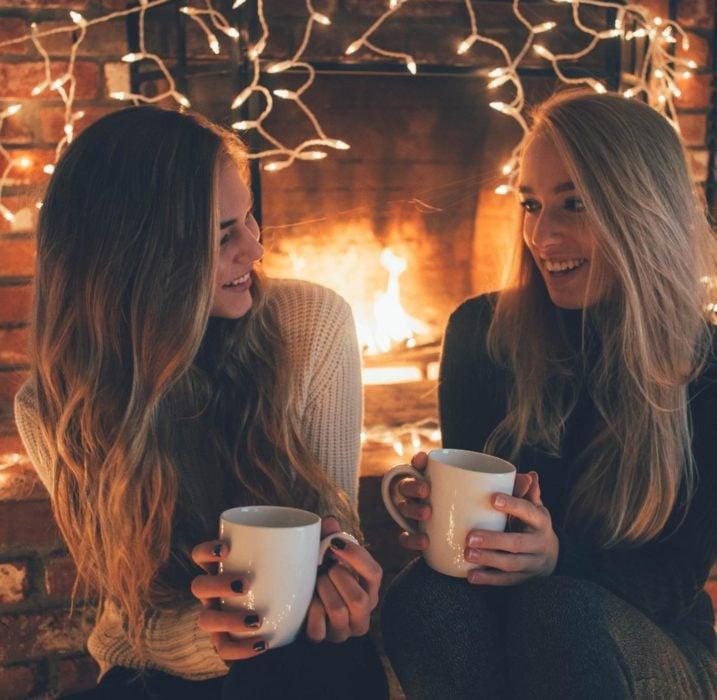 Mujeres rubias con tazas en chimenea con luces