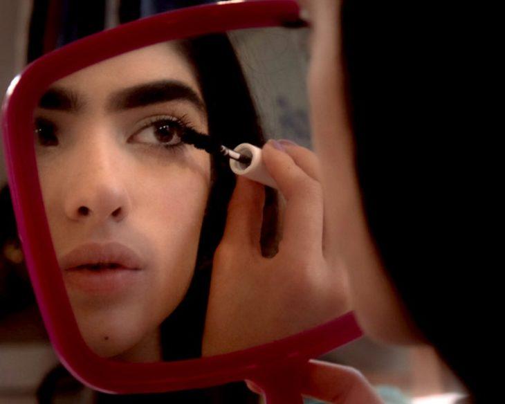 mujer de cejas grandes se arregla en el espejo