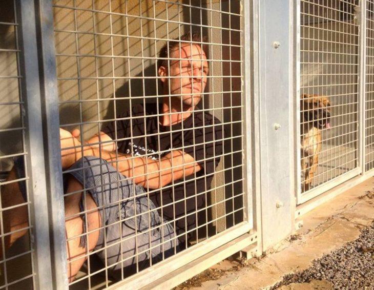 hombre sentado en el suelo dentro de una jaula