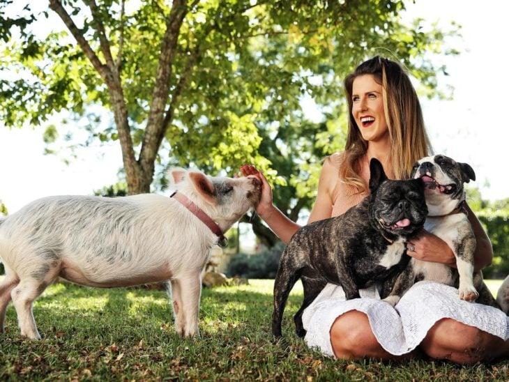 mujer rubia con cerdo y perros