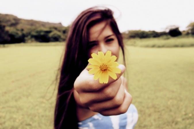 mujer con flor en la mano