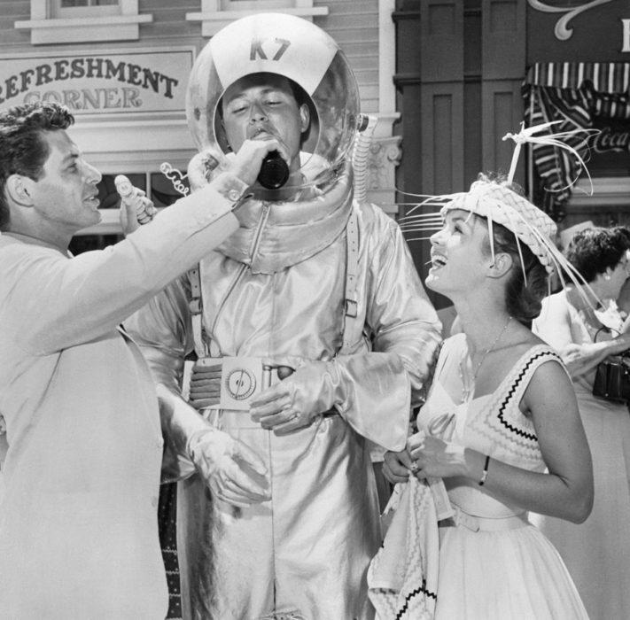 Actor dandole una bebida a un austronauta en disneyland en 1955