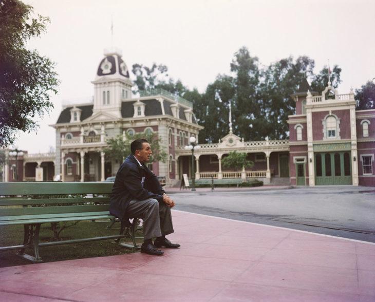 Walt disney sentado sobre una banca observando su parque de diversiones