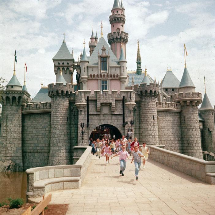 Niños corriendo por la entrada del castillo de la bella durmiente para entrar a disneyland
