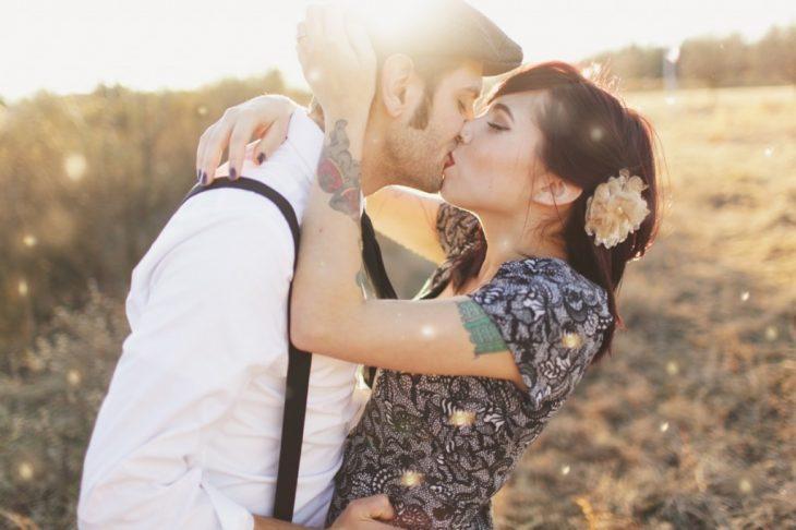 Chica con tatuajes besando a su novio