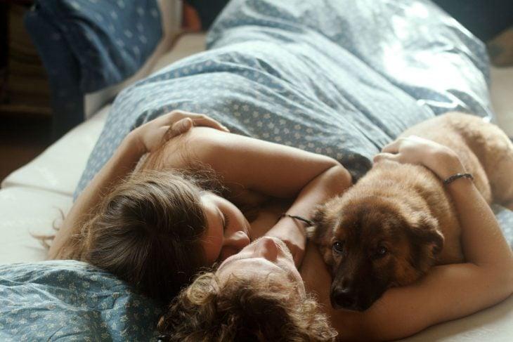 Pareja dormida con el perro en medio