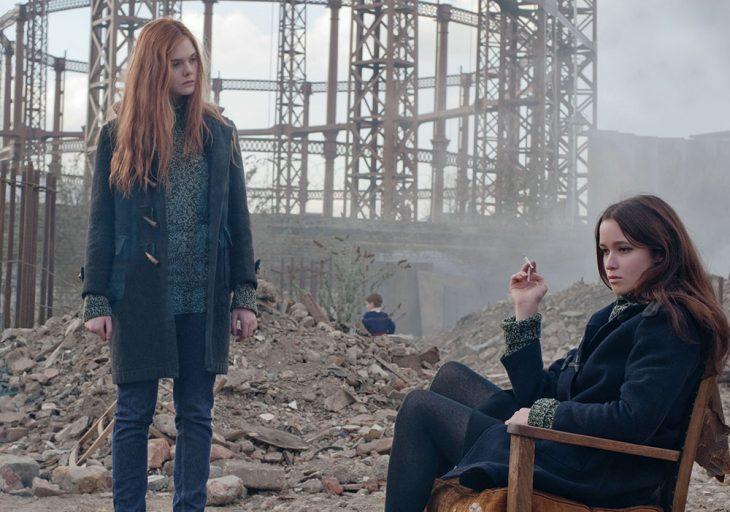 Chicas sentada entre los escombros, fumando mientras su amiga la observa