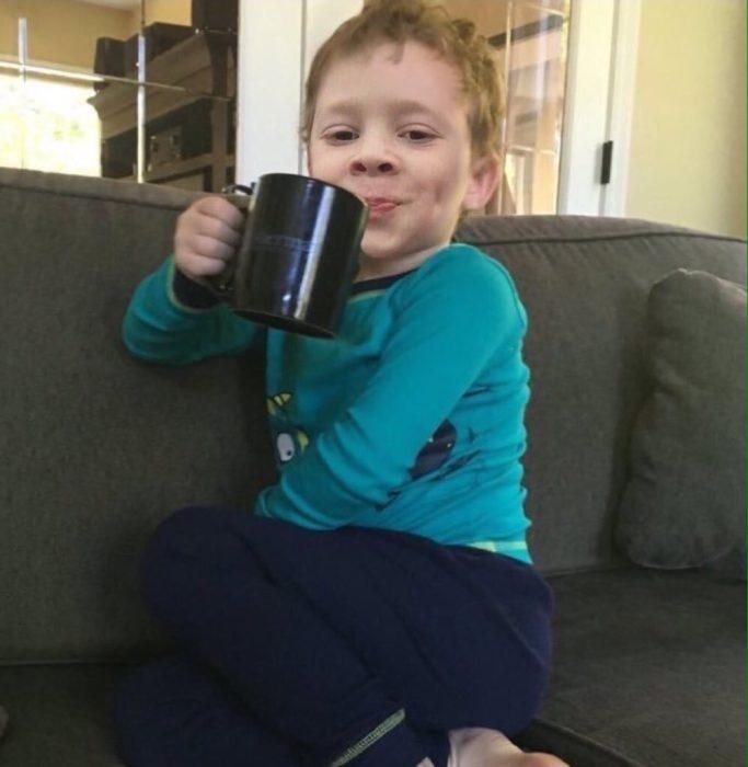 niño rubio con taza sentado y sonriendo