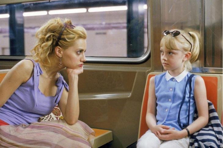 mujer blanca rubia escuchando a niña rubia sentada