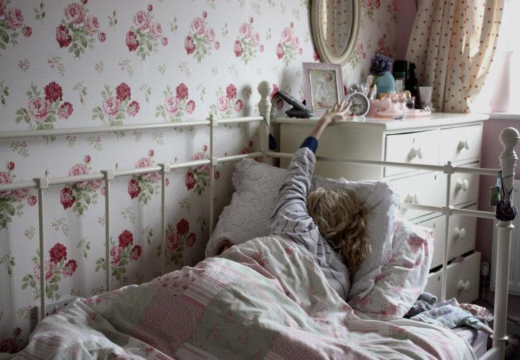 Chica apagando el despertador mientras está recostada en la cama